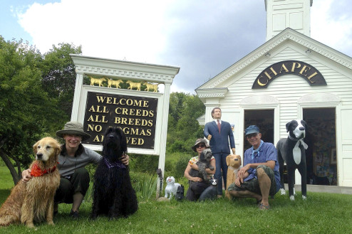 The Dog Chapel sign serves as backdrop for hundreds of family portraits.  Pictured here, Elizabeth with Fernandina and Dovekie, Ana with Tomas, and Chris nestled among Stephen's collection of dog statuettes